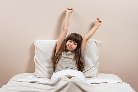 Cute little girl in pajamas is sitting on her bed stretching Stock Photo