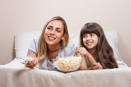 Beautiful mother and daughter in pajamas watching tv and eating popcorn together in bed. Stock Photo