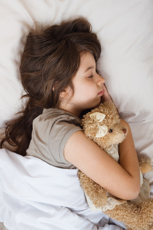 dia y noche: Beautiful little girl is sleeping with her teddy bear in bed.
