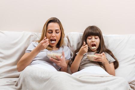 niños desayunando: desayuno saludable en la cama para la madre y la hija