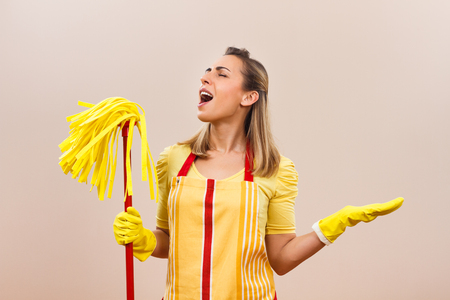 Beautiful housewife is singing while cleaning. Stock Photo