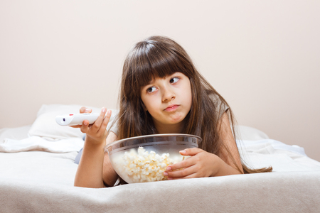 changing channels: Cute little girl is angry because there is nothing interesting on tv to watch.