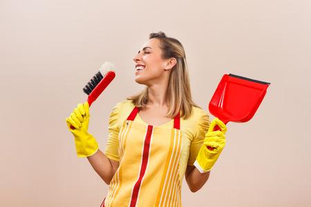 ama de casa: Hermosa ama de casa está cantando mientras se limpia.
