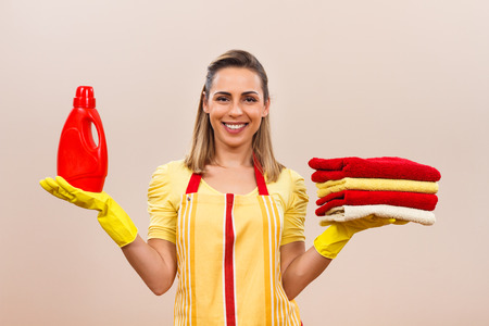 laundry detergent: Portrait of beautiful housewife holding laundry detergent and towels.