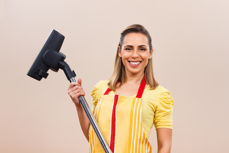 spring cleaning: Portrait of beautiful housewife holding vacuum cleaner.