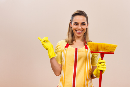 Portrait of beautiful housewife holding broom and pointing at your product.
