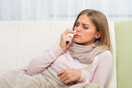 nasal drops: Woman using nasal spray Stock Photo