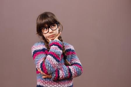 nerdy: Little nerdy girl is thinking about something. Stock Photo