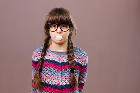 bubble gum: Cute little nerdy girl blowing  bubble gum.