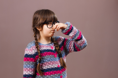feelings and emotions: Little nerdy  girl doesnt like how something smells.