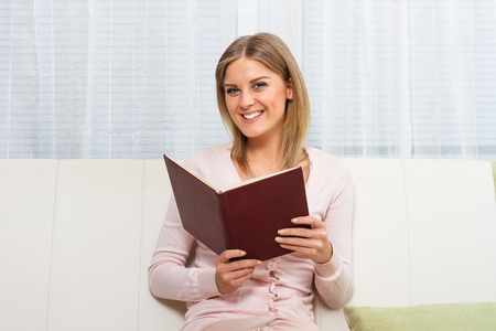 12 o'clock: Young beautiful woman is reading a book and enjoys in her free time at home.