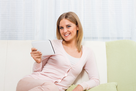 12 oclock: Young beautiful woman is sitting at sofa at home and using digital tablet.