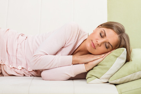 12 oclock: Beautiful woman is sleeping on sofa. Stock Photo