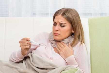 若い女性が喉の痛みを持っていると彼女は温度をチェックします。