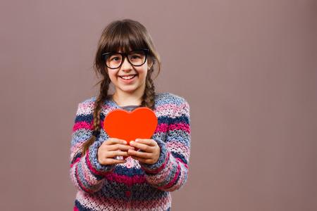 love symbols: Cute little nerdy girl is holding heart shape Stock Photo