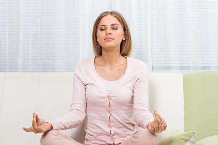 yoga pillows: Beautiful  woman is meditating at home. Stock Photo