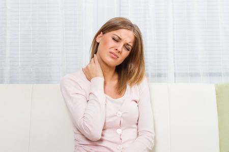 person sitting: Young woman is having neck pain. Stock Photo