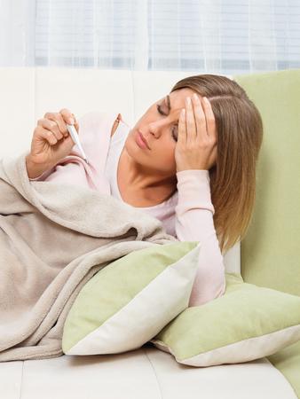 persona enferma: mujer joven est� teniendo la gripe y se verifica la temperatura. Foto de archivo