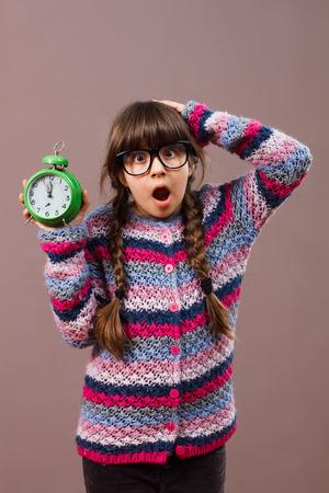 nerdy: Little nerdy girl in panic holding clock