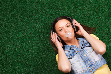 woman blowing: Cheerful young woman with headphones enjoys in music and blowing bubble while lying down on grass.