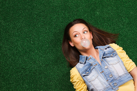 bubble gum: Cheerful young woman blowing bubble gum and thinking about something while lying on the grass.