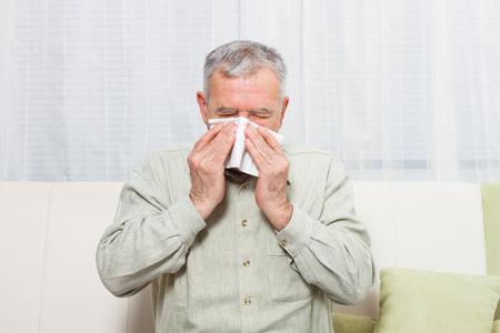 sneezing: Senior man is sneezing into handkerchief. Stock Photo