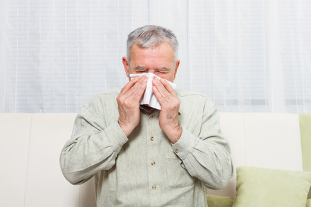 facial tissue: Senior man is sneezing into handkerchief. Stock Photo
