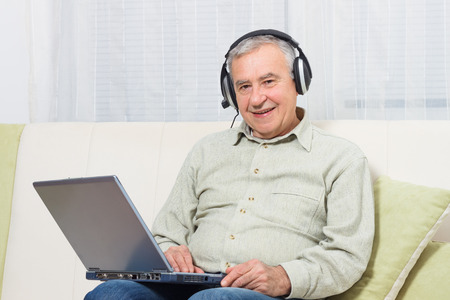 only senior men: Senior man sitting on sofa with headphones and using laptop.