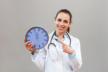 Portrait of beautiful female doctor pointing at clock to remind us that we have to take care of our health on time. Stock Photo