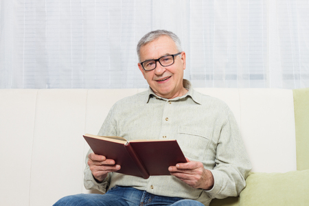 Senior man enjoys reading book.