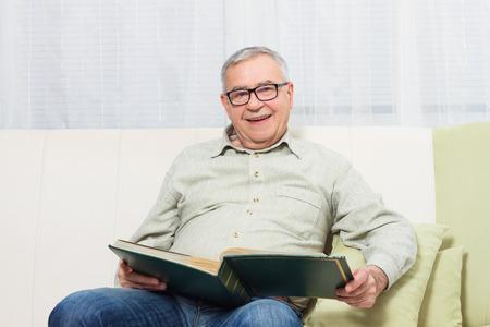 photo album: Senior man enjoys watching his photo album. Stock Photo