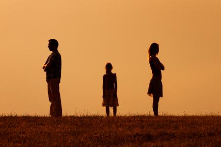 怒っている夫と真ん中に立っている娘とお互いに妻のシルエット。