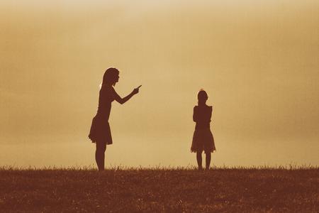 Silhouette d'une mère en colère gronder sa daughter.Image est intentionnellement avec du grain et tonique. Banque d'images - 61641330
