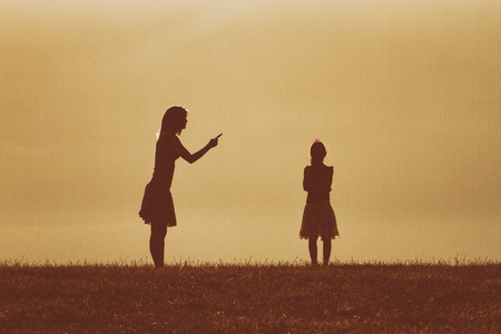 Silhouette of a angry mother scolding her daughter.Image is intentionally with grain and toned. Stock Photo