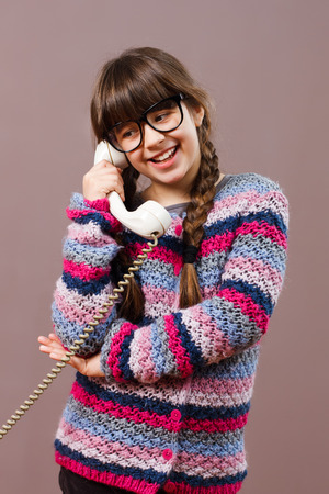 old fashioned rotary phone: Cute little nerdy girl is talking with someone on the phone.