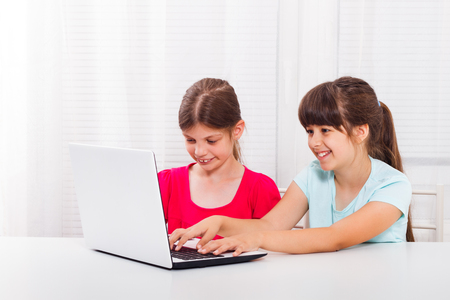 Cute little girls are sitting and using laptop.