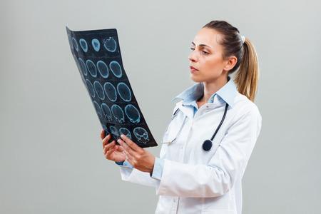 Bautiful female doctor examining x-ray.
