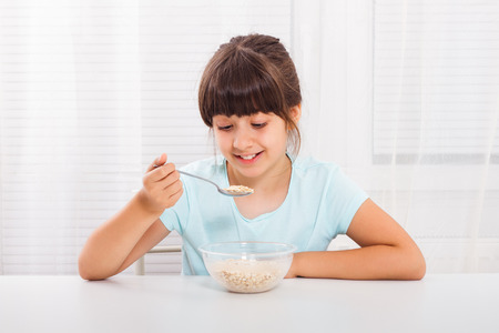 processed grains: Cute little girl is sitting and eating cereals for breakfast.