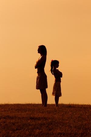 Silhouette einer wütenden Mutter und Tochter, die auf einander. Standard-Bild