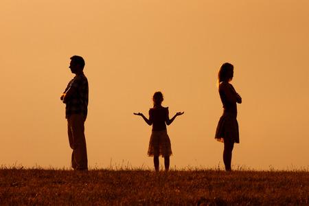 Silueta de un marido enojado y mujer el uno del otro con su hija de confusión de pie en el medio.