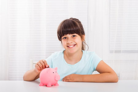 Cute little girl putting coin into piggy bank.