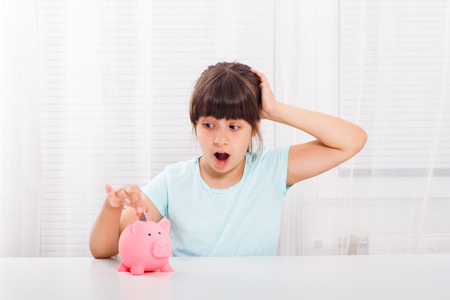 Cute little girl is in panic because of her savings. Stock Photo