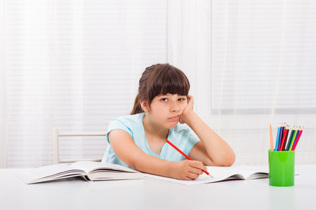Sad little girl must stay at home and do her homework,but she would rather play outside. Stock Photo