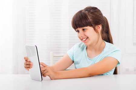 Cute little girl is sitting and using digital tablet.