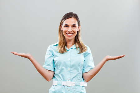 Portrait of beautiful nurse looking at camera and gesturing. Stock Photo