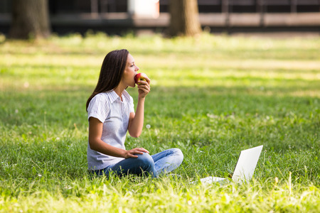 Beautiful businesswoman is eating apple and resting from work at the park.