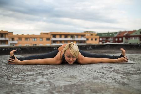 buena postura: Beautiful woman practicing yoga on the roof. Foto de archivo