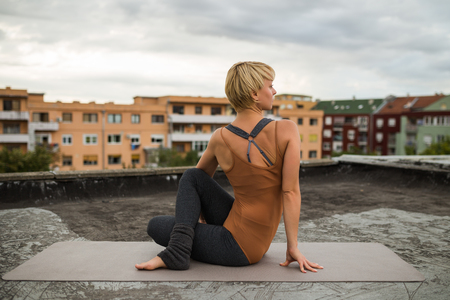 buena postura: Beautiful woman practicing yoga on the roof. Foto de archivo