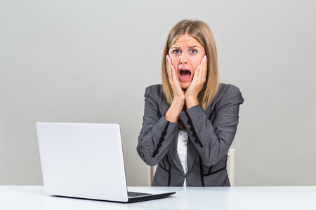 Businesswoman with laptop sitting at the table and she is in panic. Stock Photo