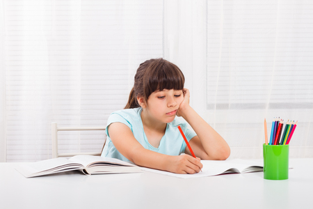 would: Sad little girl must stay at home and do her homework,but she would rather play outside. Stock Photo